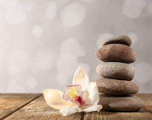 Spa stones and white orchid on wooden table on light background