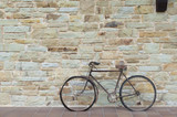 Antique or retro oxidized bicycle outside on a stone wall