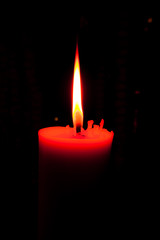 A burning candle in dark.