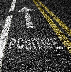 positive and arrow on the asphalt road