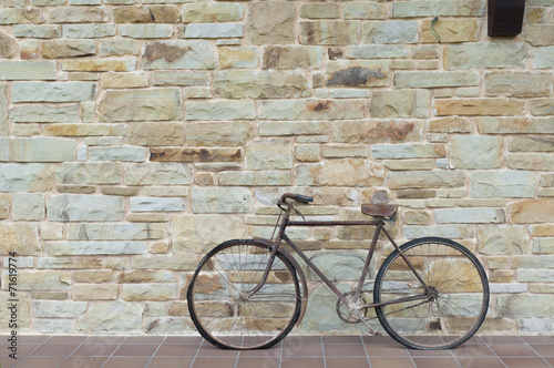 Tuinposter Fiets Antique or retro oxidized bicycle outside on a stone wall