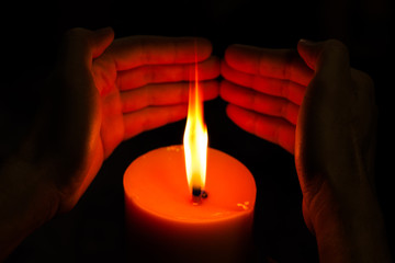 hands holding a burning candle.