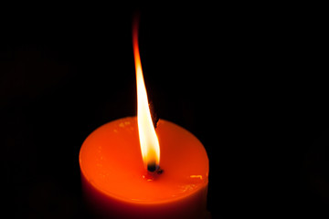 A burning candle in dark