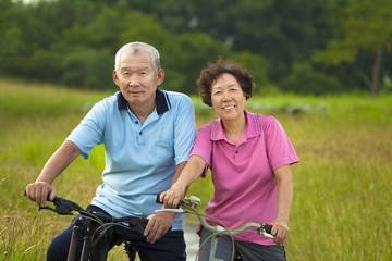 Happy Asian seniors couple biking in Park.
