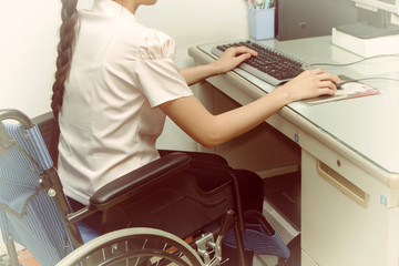 Asia woman in wheelchair working on computer in the office