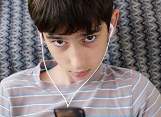 Teen listens youth music through headphones