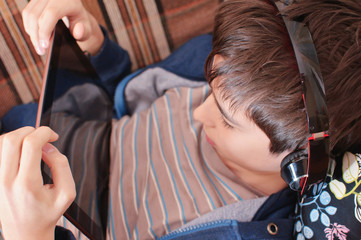 boy with headphones looks on the tablet