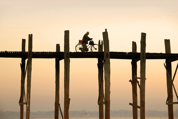 cyclist is driving over U Bein's Bridge