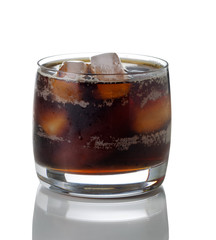 Freshly poured dark soda with ice in glass