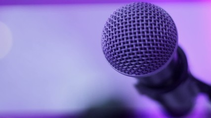Close up of Microphone on Stage with lighting in purple tones