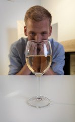 Addicted man looking at glass of wine