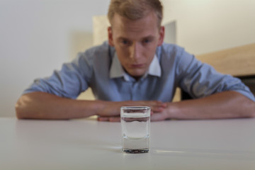 Young man looks at a glass of vodka