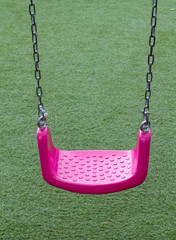 Pink swing on green grasses