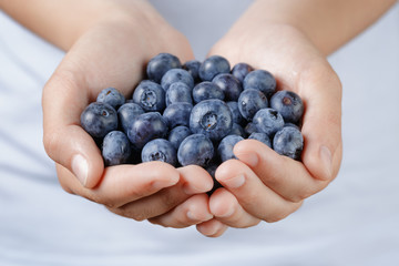 fresh washed blueberries in female teen hands