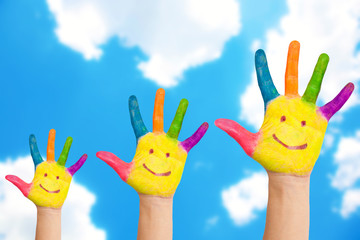 Smiling family hands on a sky background.
