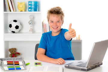 happy boy is doing homework with book and computer