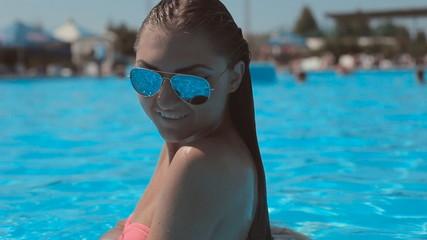 Sexy girl in bikini with long hair floating in a pool
