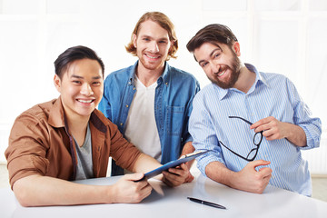Three happy young businessmen with document on clipboard