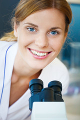 Portrait of beautiful young doctor  with microscope.