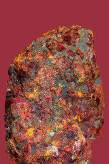 Realgar ,arsevic mineral   on a bordeaux  background