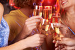 Five hands raising champagne flutes in a toast