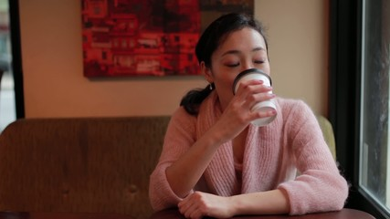 Young Asian woman drinking coffee in a cafe