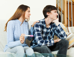 worried woman with pregnancy test with unhappy man
