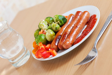 sausages with broccoli on white plate