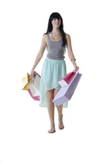 Young pretty shopping girl walking with colorful parcels