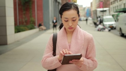 Young Asian woman walking using tablet pc on street