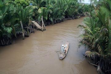 Мужчина плывет в лодке по реке Меконг