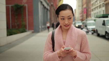 Young Asian woman walking texting cellphone on street