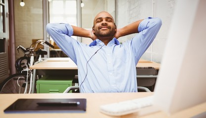 Relaxed businessman listening music at desk
