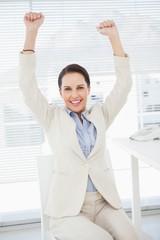 Smiling businesswoman celebrating at work
