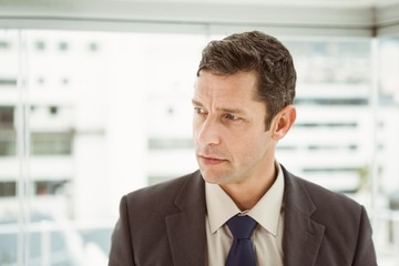 Thoughtful businessman looking away at office