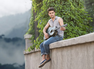 Young guitarist sitting on parapet and looking at camera