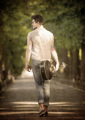 Young guitarist walking away along the boulevard, view from back