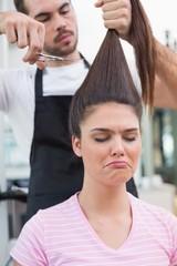 Sad brunette getting her hair cut