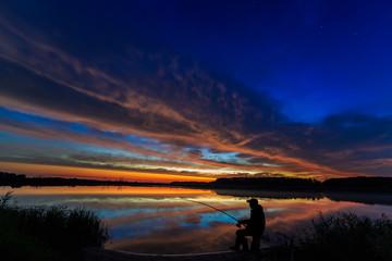 Fisherman fishing rod at dawn on the lake.