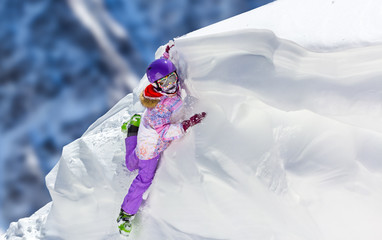 Little Girl in bright ski clothes climbs a snow cornice