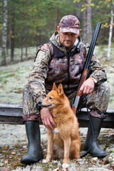 hunter with a dog sitting in the forest
