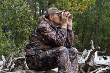 hunter with binoculars looks out the game