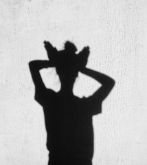 Shadow of girl holding hands on her head