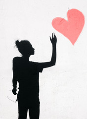 Portrait of young woman with  Heart on wall background
