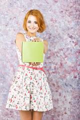 Beautiful slim girl in a short dress holding gift box.