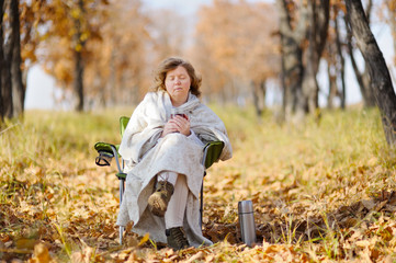 Young woman in autumn, wrapped up against the cold, cool hot tea