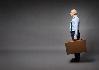 old man ready to leave with suitcase on hand