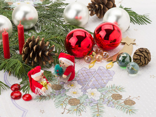 Weihnachtstisch mit Figuren, Kugeln und Tannengrün