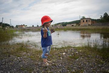 Ребенок у озера выбирает камень