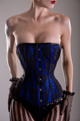 Busty burlesque woman in black and blue corset